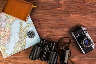 Kamera und Fernglas mit Kompass auf Karte und Tagebuch