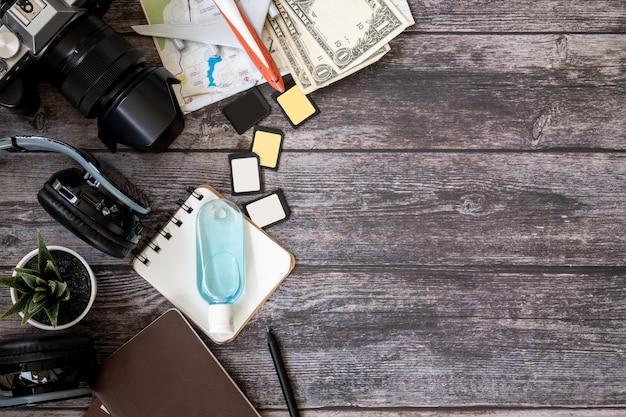 Kamera und notizbuch mit reisewerkzeugen auf einem holztisch