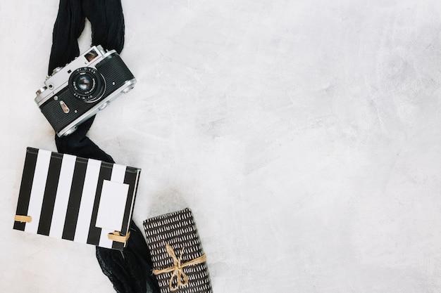 Kamera und tuch nahe notizbuch und geschenk