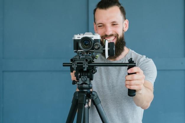 Kameramann beruf. lebensstil und hobby. mann, der filmmaterial mit kamera auf halter und stativ schießt. moderne geräte und tools für das video-streaming-konzept.