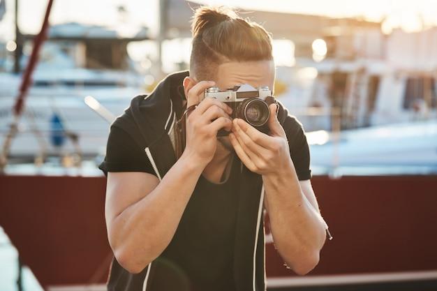 Kameramann versucht still zu halten, um vögel nicht zu erschrecken. porträt des fokussierten jungen männlichen fotografen, der durch kamera und stirnrunzeln schaut, fokussiert auf modell während der fotosession nahe der küste im hafen