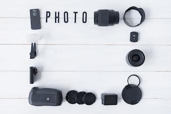 Kameraobjektiv mit Fotografiezubehör und Fototext vereinbarte auf weißem Holztisch