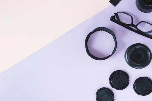 Kameraobjektiv; verlängerungsringe mit kamerazubehör und brille auf doppeltem hintergrund