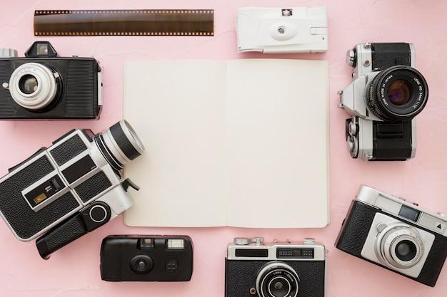 Kameras und filmstreifen um notizbuch
