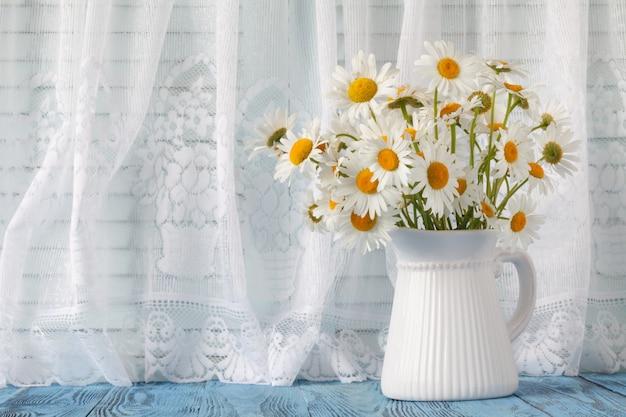 Kamille in der vase auf der fensterbank