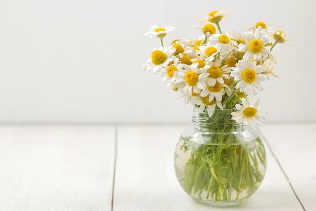Kamille. medizinische kleine kamillenblüten in einer vase auf einem weißen holztisch. platz für text