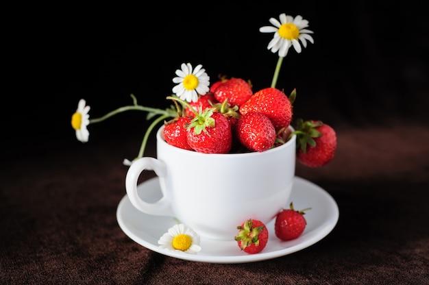 Kamille und erdbeeren in der tasse