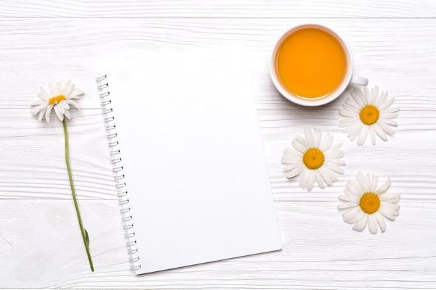 Kamillenblüten, notizbuch mit platz für text, tasse mit tee auf weiß