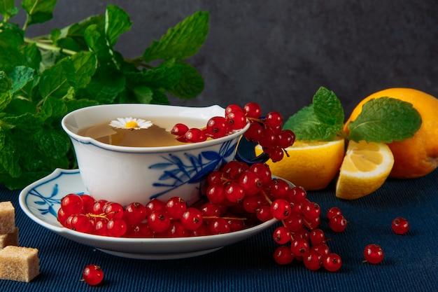 Kamillentee in tasse und sauce mit zitrone mit scheiben, frischen roten beeren, braunem zucker und blättern auf grauem stuck und dunkelblauem tischset-hintergrund. vertikale seitenansicht