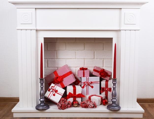Kamin mit weihnachtskisten und kerzen auf holzboden