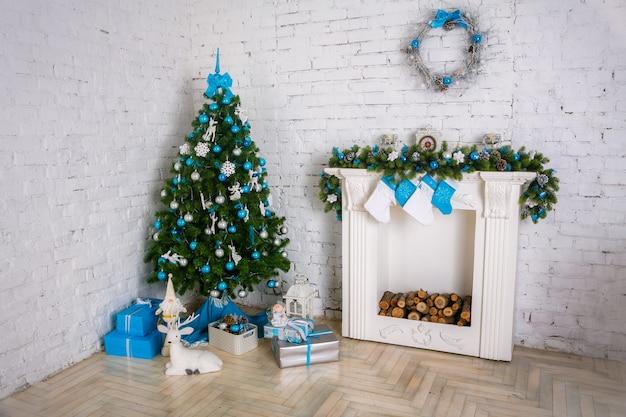 Kamin und geschmückter weihnachtsbaum mit geschenk