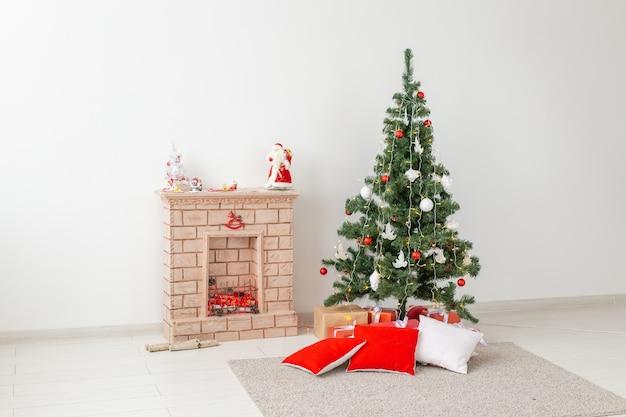 Kamin und weihnachtsbaum mit geschenken im wohnzimmer.