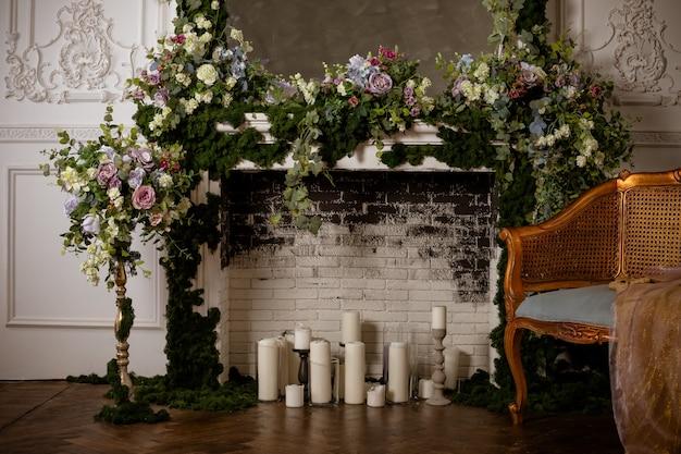 Kamin voller blumen und kerzen. heiratender romantischer kamin verziert mit frühlingsblumen, kranz, kerzen backsteinmauer blumendekoration