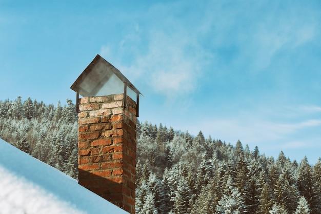 Kaminziegelsteinrohr auf dem hintergrund des schnees bedeckte wald und blauen himmel.