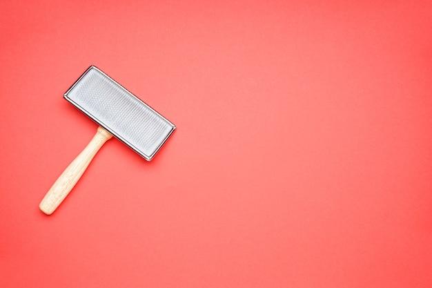 Kamm für hunde auf rotem grund, platz für text. bürste zum pflegen von wolle. flach liegen.