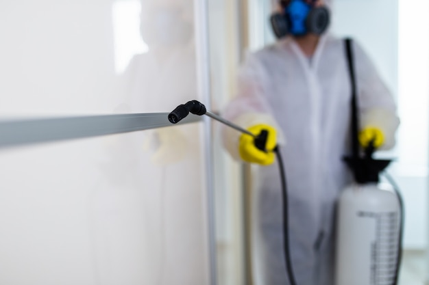 Kammerjäger in arbeitskleidung sprüht pestizide mit sprühgerät.