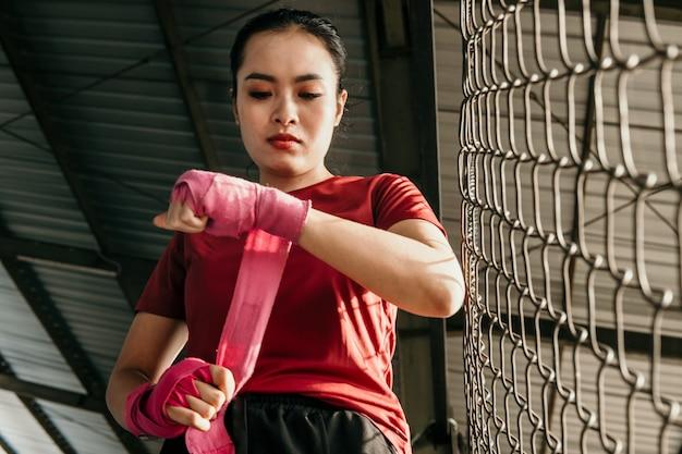 Kampf frau vorbereitung. kurzer schuss einer zerrissenen asiatischen kämpferin, die ihre hände einwickelt