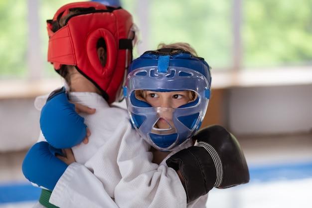 Kampf mit freund. dunkeläugiger junge mit schutzhelm und handschuhen im kampf mit freund