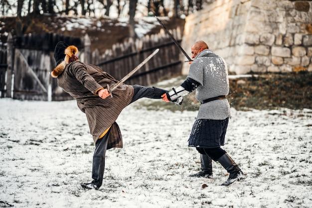 Kampf zweier krieger in rüstung mit waffen, die mit schwertern im schnee kämpfen