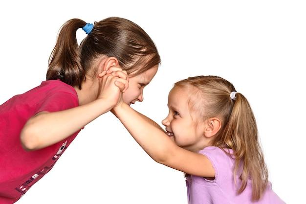 Kampf zwischen zwei kleinen mädchen kinder, die auf weißem hintergrund herumalbern