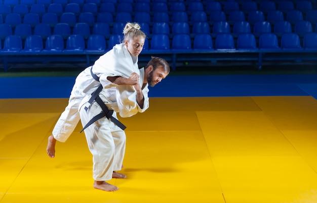 Kampfkunst. sparsame portner. sport mann und frau im weißen kimono zug judo wirft und fängt in der sporthalle