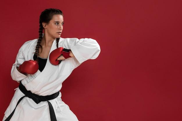 Kampfkunstkaratemädchen mit hintergrund des schwarzen gürtels und des exemplarplatzes