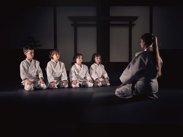 Kampfkunsttrainer, der vor den schülern mit den weißen kimonos sitzt