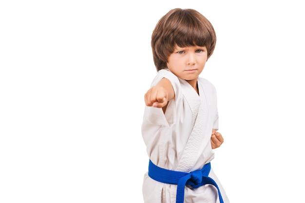 Kampfsport-junge. kleiner junge, der karate trainiert, während er auf weißem hintergrund isoliert ist