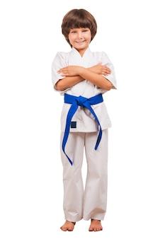 Kampfsport-junge. voller länge des kleinen jungen, der karate trainiert, während er auf weißem hintergrund isoliert ist