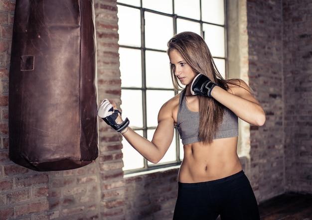 Kampftraining. frau schlägt die schwere boxsack