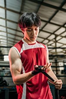 Kampfvorbereitung. kurzer schuss eines zerrissenen asiatischen kämpfers, der seine hände einwickelt