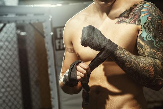 Kampfvorbereitung. kurzer schuss eines zerrissenen tätowierten kämpfers, der seine hände umwickelt