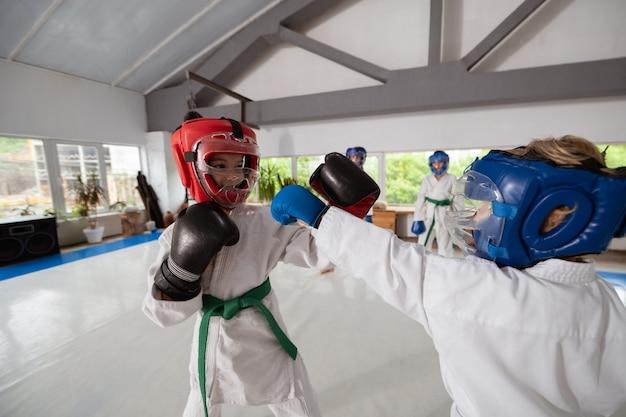 Kampfzeit. aktive sportliche jungen und mädchen, die miteinander kämpfen, während sie kampfkünste üben