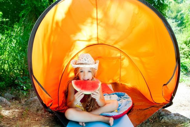 Kampierendes kindermädchen im zelt wassermelonescheibe essend
