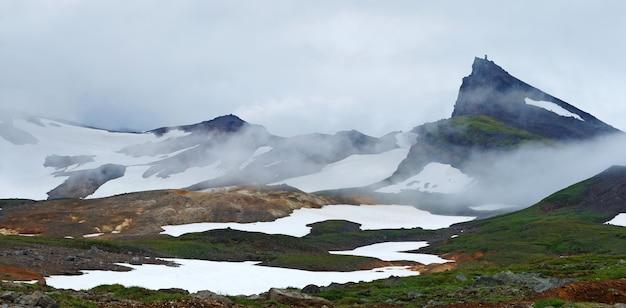 Kamtschatka. foto von bergen und schnee. grünes gras, geysire