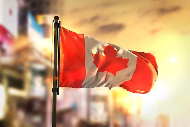 Kanada-flagge gegen stadt verschwommener hintergrund bei sonnenaufgang-hintergrundbeleuchtung