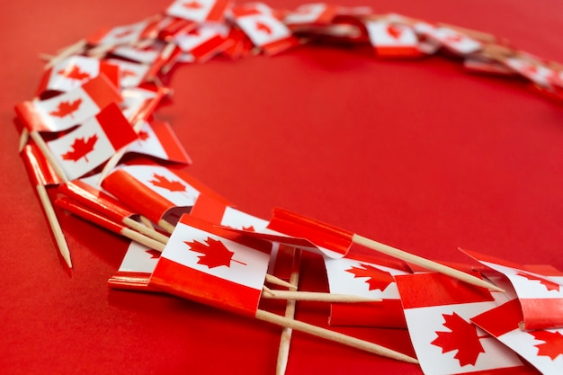 Kanadische flaggen flach legen zusammensetzung mit kopienraum auf dem roten hintergrund happy canada day