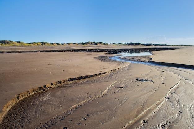 Kanal im sand am strand, der durch die ebbe entstanden ist