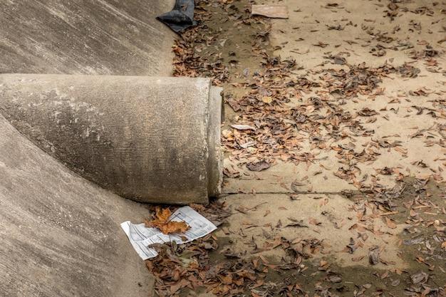 Kanalisationsrohrsystem aus beton mit schutt und laub