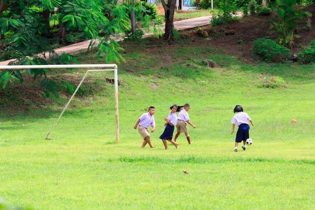 Kanchanaburi, thailand - 25. august 2017: thailändischer student, der fußball auf grünem feld in der schule spielt.