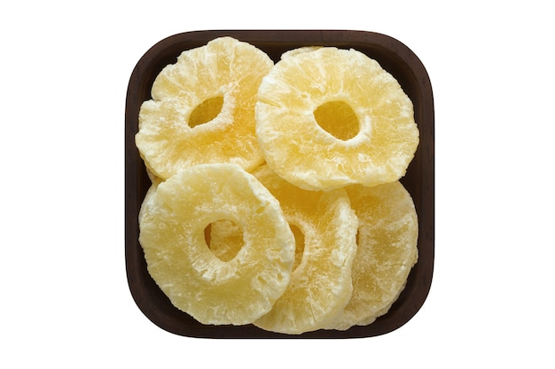 Kandierte frucht, ringananas in quadratischer schüssel lokalisiert auf weißer wand. bio-lebensmittel, draufsicht.