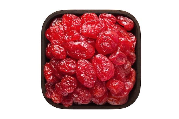 Kandierte früchte, getrockneter hartriegel mit zucker in quadratischer schüssel isoliert auf weißem hintergrund. bio-lebensmittel, ansicht von oben.