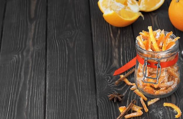 Kandierte orangenschale in zucker und orangen auf einem dunklen holztisch