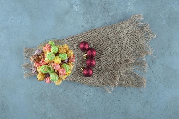 Kandiertes popcorn gestapelt in einem glashalter neben weihnachtskugeln auf marmoroberfläche