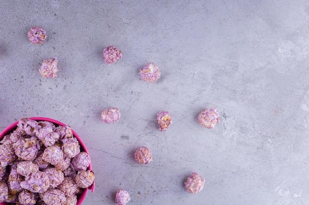 Kandiertes popcron im inneren und verstreut um einen kleinen eimer auf marmorhintergrund. foto in hoher qualität