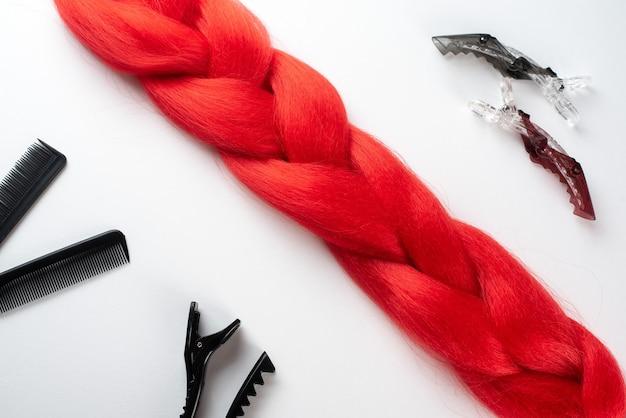 Kanekalon-haar auf weißer oberfläche mit kämmen und haarschmuck