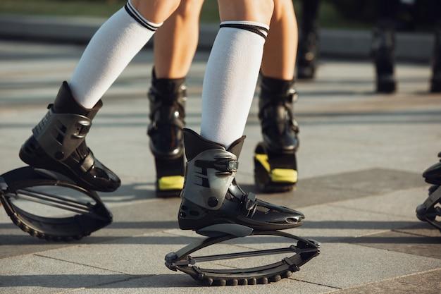 Kangoo-schuhe, sportbekleidung zum springen hautnah. frauenbeine an der straße am sonnigen sommertag. hochspringen, aktive bewegung, action, fitness und wellness. fit weibliche models während des trainings.