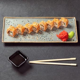 Kani hot sushi roll mit soja, wasabi, ingwer und schwarzem essstäbchen