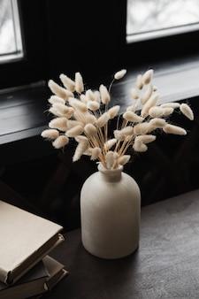 Kaninchen-bunny-tail-gras-bouquet in topfvase, bücherstapel auf massivem holztisch gegen fenster.