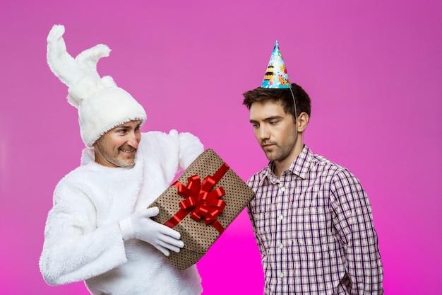 Kaninchen, das dem betrunkenen mann geburtstagsgeschenk über lila wand gibt.